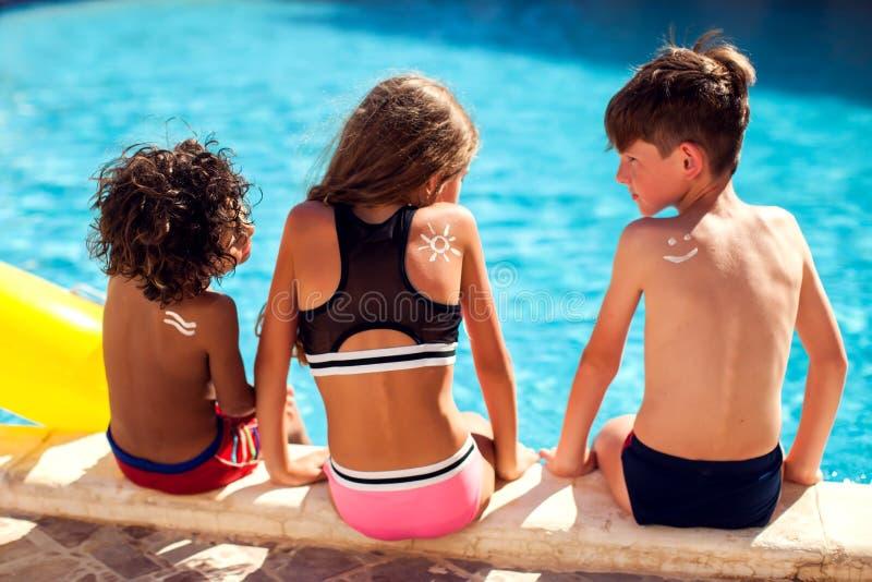Τα παιδιά με την προστασία ήλιων αποβουτυρώνουν στο δέρμα στη λίμνη Παιδιά, έννοια καλοκαιριού, διακοπών και υγειονομικής περίθαλ στοκ φωτογραφία