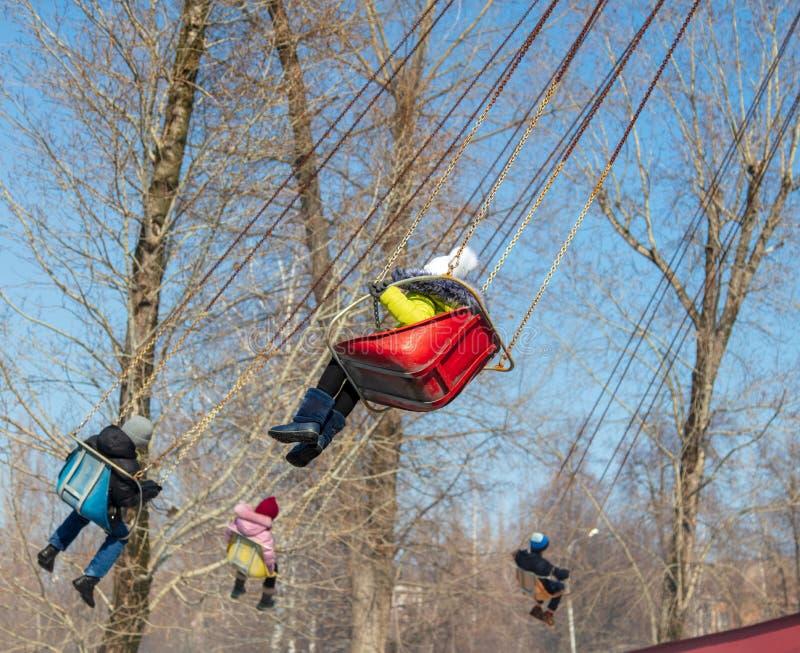 Τα παιδιά οδηγούν στο ιπποδρόμιο στο πάρκο στοκ φωτογραφίες με δικαίωμα ελεύθερης χρήσης