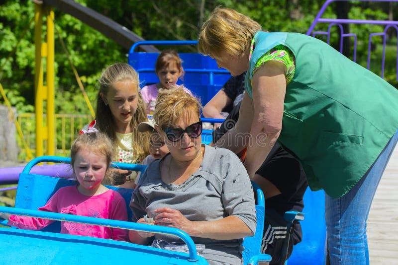 Τα παιδιά οδηγούν στο ιπποδρόμιο στην παιδική χαρά των παιδιών στοκ φωτογραφία με δικαίωμα ελεύθερης χρήσης
