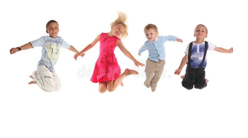 τα παιδιά ομαδοποιούν το ευτυχές άλμα στοκ εικόνες