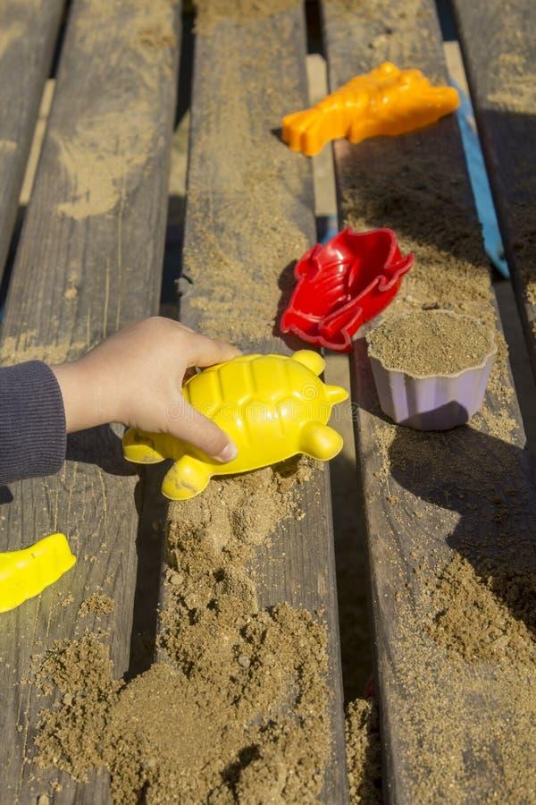 Τα παιδιά παίζουν με τα παιχνίδια άμμου σε έναν ξύλινο πίνακα στοκ φωτογραφία με δικαίωμα ελεύθερης χρήσης