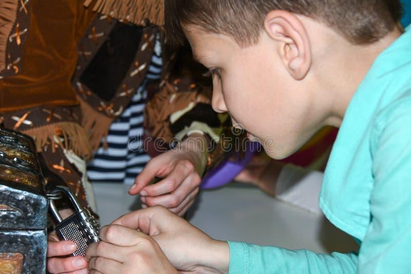 Τα παιδιά παίζουν μια αναζήτηση, στήθος θησαυρών, ανοικτή κλειδαριά σιδήρου, παιχνίδι, ψυχαγωγίες, λούνα παρκ, παιχνίδι ρόλου, ομ στοκ φωτογραφία