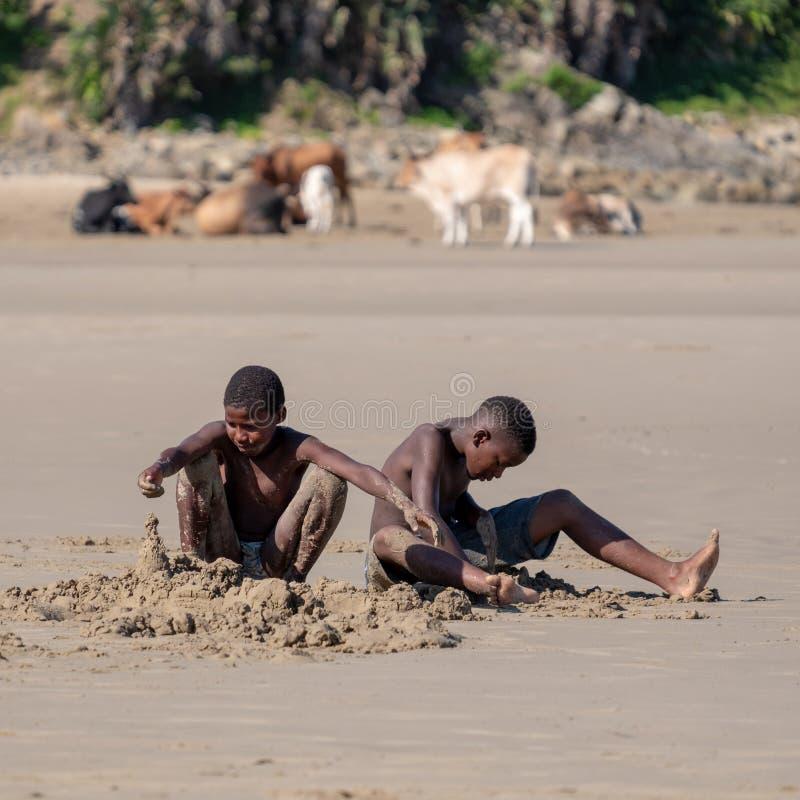 Τα παιδιά παίζουν στην άμμο στη δεύτερη παραλία, λιμένας ST Johns στην άγρια ακτή στο Transkei, Νότια Αφρική στοκ εικόνα