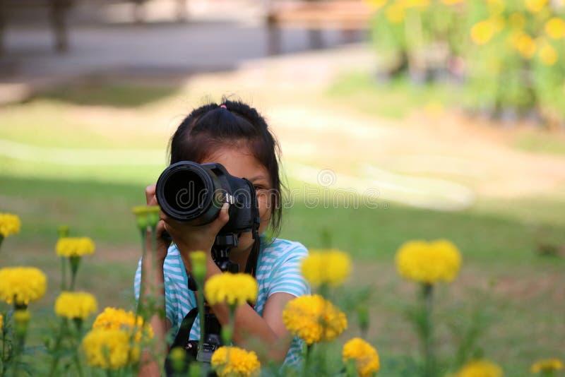 Τα παιδιά παίρνουν τη φωτογραφία του κίτρινου λουλουδιού από τη κάμερα dslr στοκ φωτογραφίες