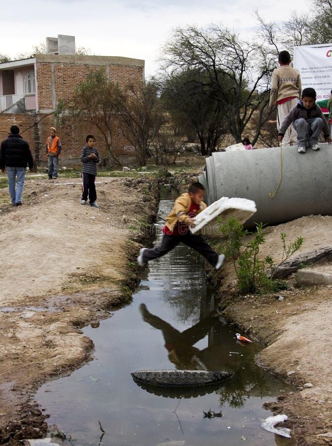 τα παιδιά σκάβουν το άλμα πέρα από τα λύματα στοκ εικόνα με δικαίωμα ελεύθερης χρήσης