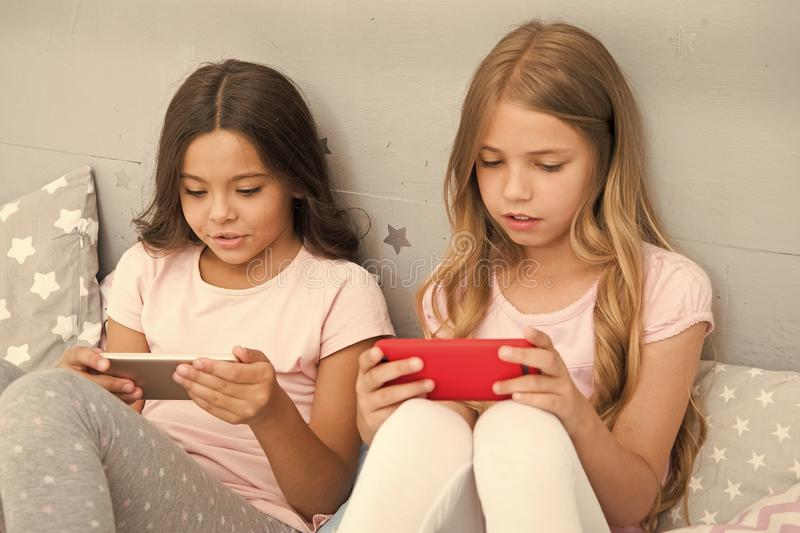 Τα παιδιά στην πυτζάμα αλληλεπιδρούν με τα smartphones Εφαρμογή για τη διασκέδαση παιδιών Σερφ Διαδικτύου και γονικός συμβουλευτι στοκ εικόνα