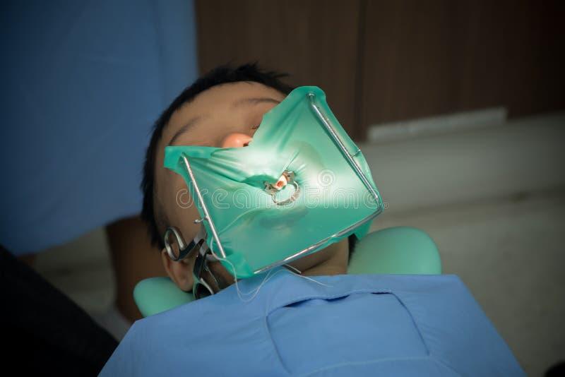 Τα παιδιά στον οδοντίατρο προεδρεύουν τρυπώντας με τρυπάνι δόντια γιατρών οδοντιάτρων ένα αγόρι στοκ εικόνες με δικαίωμα ελεύθερης χρήσης