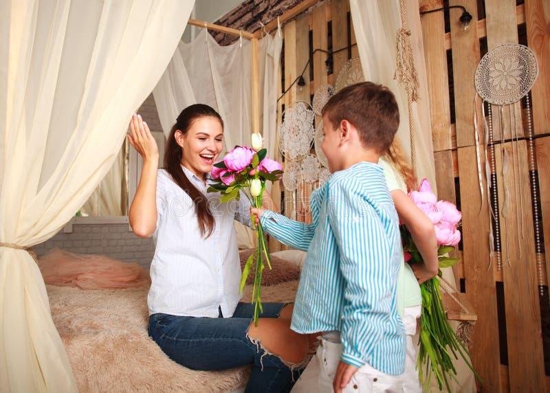 Τα παιδιά συγχαίρουν τη μητέρα δίνουν την ανθοδέσμη λουλουδιών της στοκ εικόνα