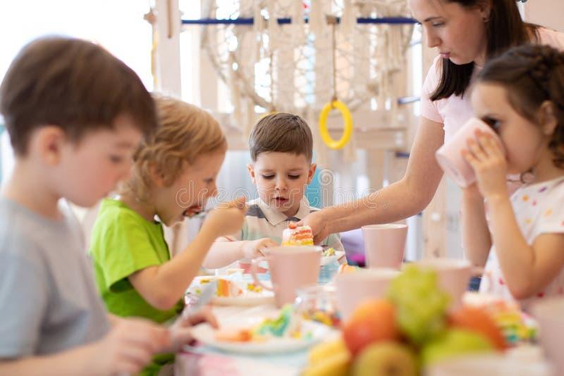 Τα παιδιά τρώνε στις διακοπές στη φύλαξη στοκ εικόνα με δικαίωμα ελεύθερης χρήσης