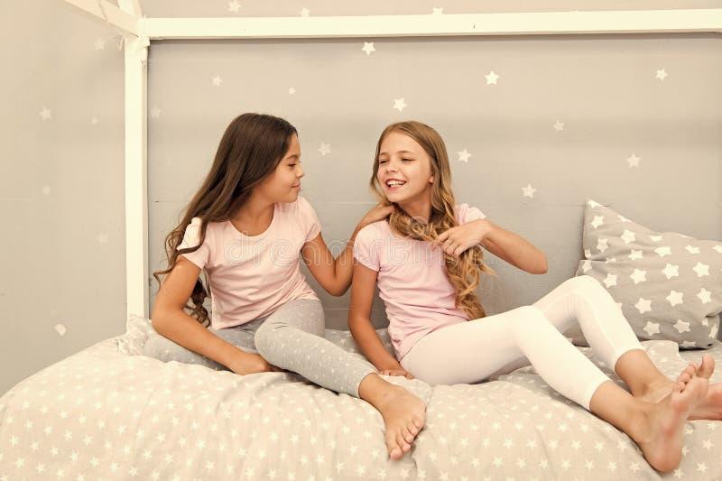Τα παιδιά χαλαρώνουν και έχοντας τη διασκέδαση το βράδυ Ελεύθερος χρόνος αδελφών Τα κορίτσια στις χαριτωμένες πυτζάμες ξοδεύουν τ στοκ εικόνες