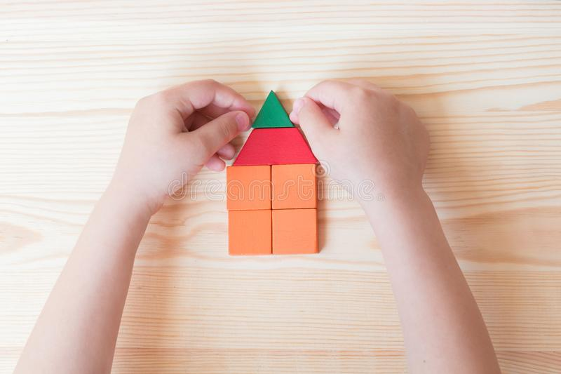 Τα παιδικά παιχνίδια με τους χρωματισμένους φραγμούς, δημιουργούν ένα σπίτι σε ένα ελαφρύ ξύλινο υπόβαθρο στοκ φωτογραφία με δικαίωμα ελεύθερης χρήσης