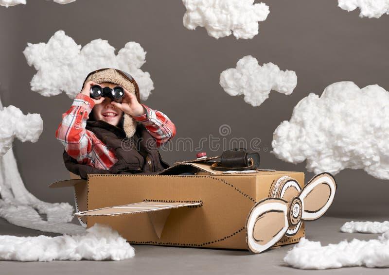 Τα παιχνίδια αγοριών σε ένα αεροπλάνο φιαγμένο από κουτί από χαρτόνι και όνειρα να γίνουν πειραματικά, καλύπτουν cottonwool σε έν στοκ εικόνα με δικαίωμα ελεύθερης χρήσης