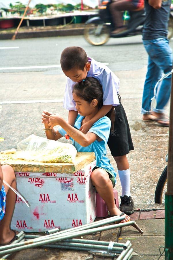 Τα παιδιά δένουν τα λουλούδια στην αγορά λουλουδιών στη Μπανγκόκ στοκ εικόνες