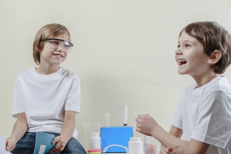 Τα παιδιά έχουν τη διασκέδαση κάνοντας τα πειράματα επιστήμης η εκπαίδευση έννοιας βιβλίων απομόνωσε παλαιό στοκ εικόνες