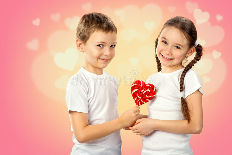 Τα παιδιά, αγόρι δίνουν σε μια μικρή καραμέλα κοριτσιών το κόκκινο lollipop στη μορφή καρδιών στο ρόδινο υπόβαθρο στοκ εικόνες