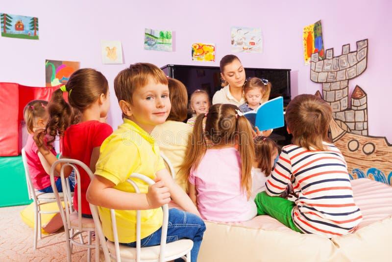 Τα παιδιά ακούνε το βιβλίο ανάγνωσης αφήγησης δασκάλων στοκ φωτογραφίες