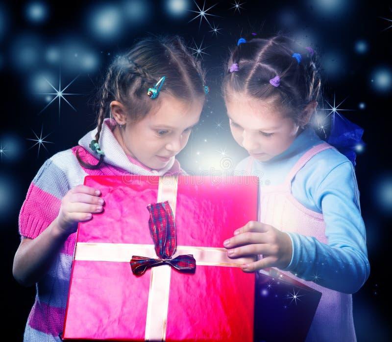 Τα παιδιά ανοίγουν ένα μαγικό παρόν κιβώτιο στοκ εικόνες