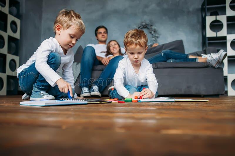 Τα παιδιά επισύρουν την προσοχή τους δείκτες στο πάτωμα ενώ οι γονείς χαλαρώνουν τον καναπέ στοκ εικόνες