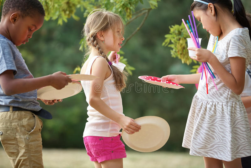Τα παιδιά διανέμουν τα πιάτα σε ένα κόμμα στοκ εικόνα με δικαίωμα ελεύθερης χρήσης