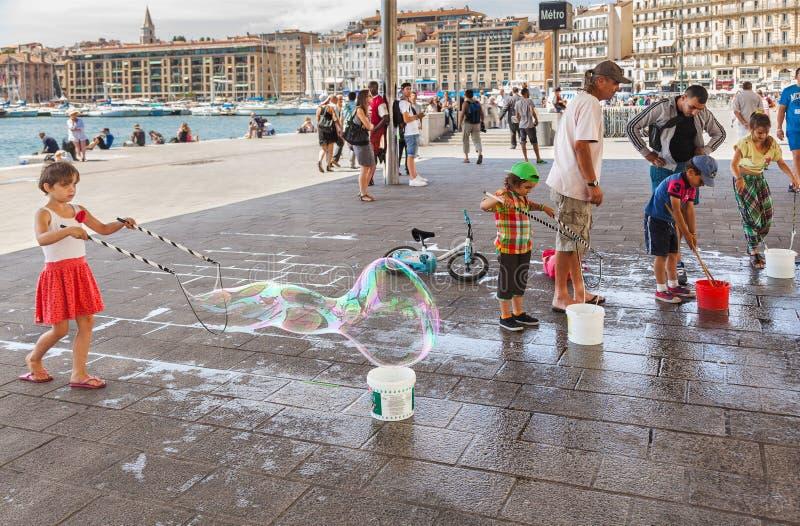 Τα παιδιά διογκώνουν τις τεράστιες φυσαλίδες σαπουνιών στοκ φωτογραφία