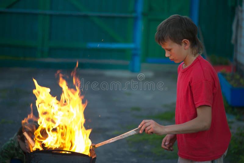 Τα παιδιά παίζουν με τη φωτιά στη σχάρα στοκ φωτογραφία