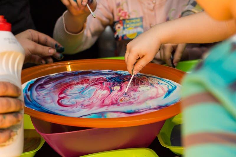 Τα παιδιά πειραματίζονται με τα χρώματα στα πιάτα στοκ φωτογραφία με δικαίωμα ελεύθερης χρήσης