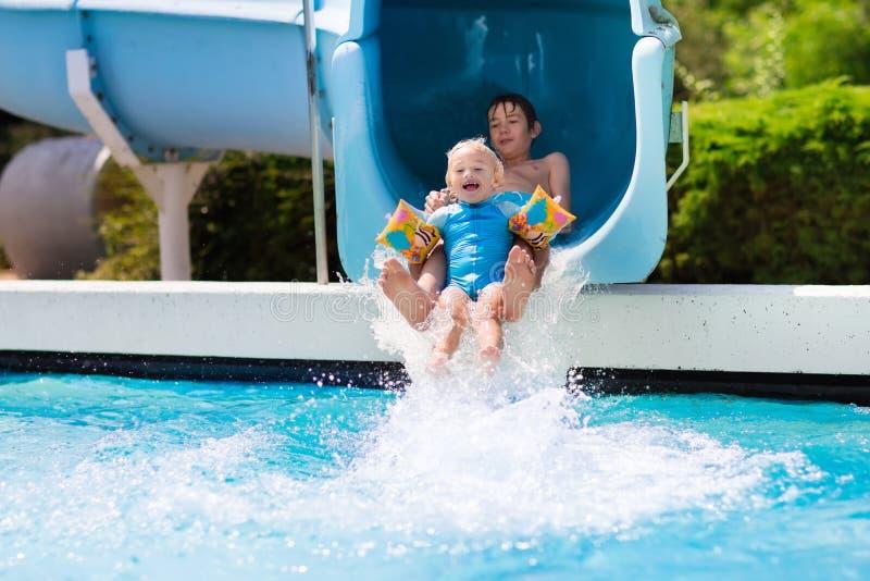 Τα παιδιά σε ένα νερό γλιστρούν μέσα την πισίνα στοκ εικόνες