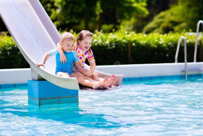 Τα παιδιά στο νερό γλιστρούν μέσα την πισίνα στοκ φωτογραφίες με δικαίωμα ελεύθερης χρήσης