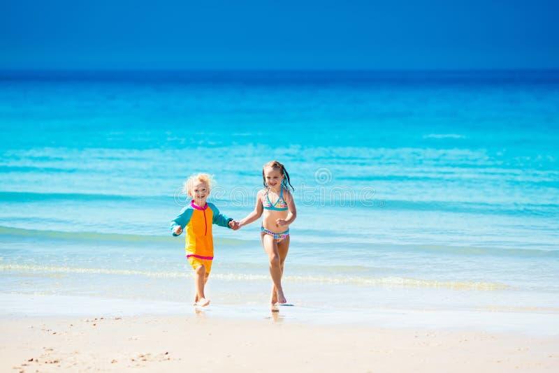 Τα παιδιά τρέχουν και παίζουν στην τροπική παραλία στοκ φωτογραφία με δικαίωμα ελεύθερης χρήσης
