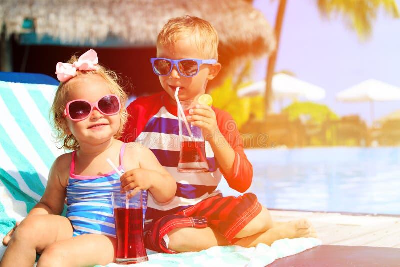 Τα παιδιά χαλαρώνουν στο τροπικά παραθαλάσσιο θέρετρο και το ποτό στοκ εικόνες