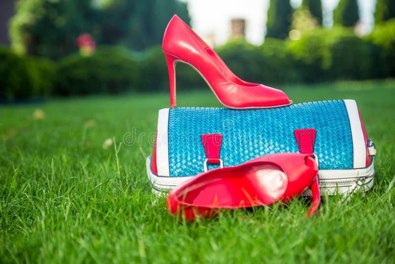 Τα παπούτσια των γυναικών είναι στην τσάντα και στο έδαφος, θερινά παπούτσια των γυναικών στοκ φωτογραφία με δικαίωμα ελεύθερης χρήσης