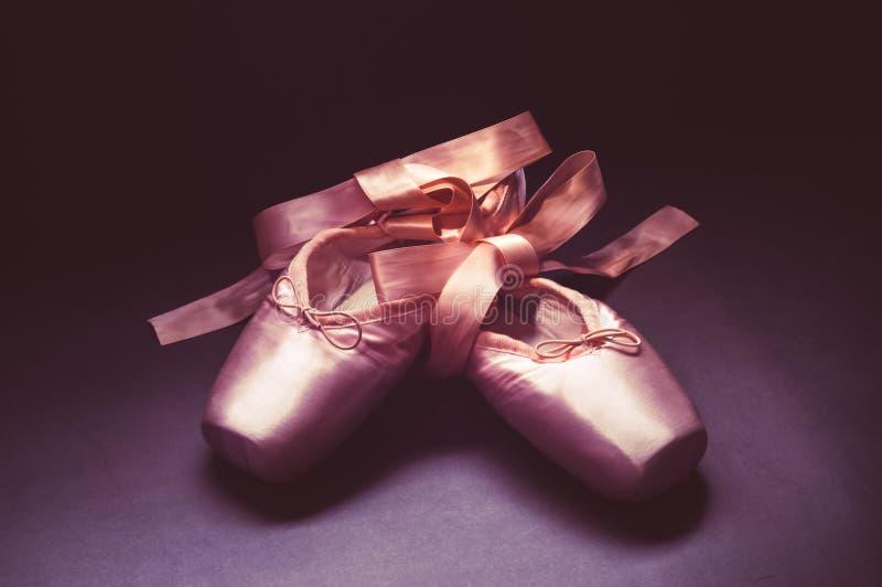 Τα παπούτσια χορού μπαλέτου παπουτσιών Pointe με ένα τόξο των κορδελλών δίπλωσαν υπέροχα σε ένα σκοτεινό υπόβαθρο στοκ φωτογραφία