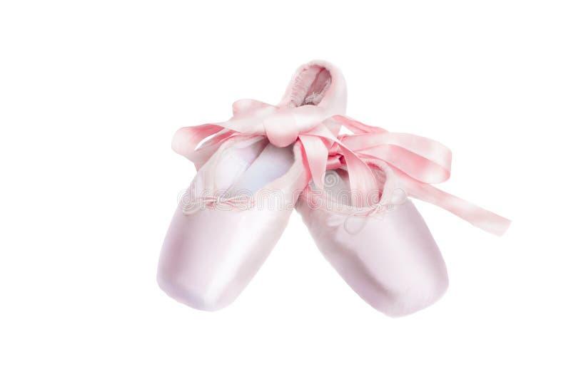 Τα παπούτσια χορού μπαλέτου παπουτσιών Pointe με ένα τόξο των κορδελλών δίπλωσαν υπέροχα σε ένα άσπρο υπόβαθρο στοκ εικόνες