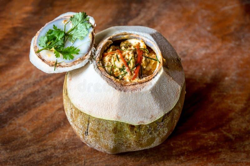 Τα παραδοσιακά ταϊλανδικά τρόφιμα έβρασαν τα θαλασσινά με την πικάντικη κόλλα κάρρυ στα φρούτα καρύδων στον ξύλινο πίνακα στον ατ στοκ εικόνες