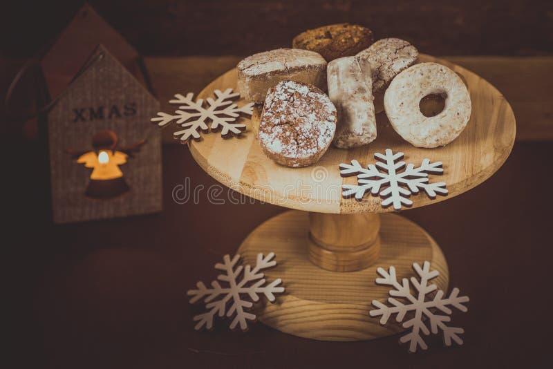 Τα παραδοσιακά ισπανικά μπισκότα Χριστουγέννων polvorones, τα nevaditos και τα mantecados σε ένα ξύλινο κέικ στέκονται, αναμμένο  στοκ φωτογραφία με δικαίωμα ελεύθερης χρήσης