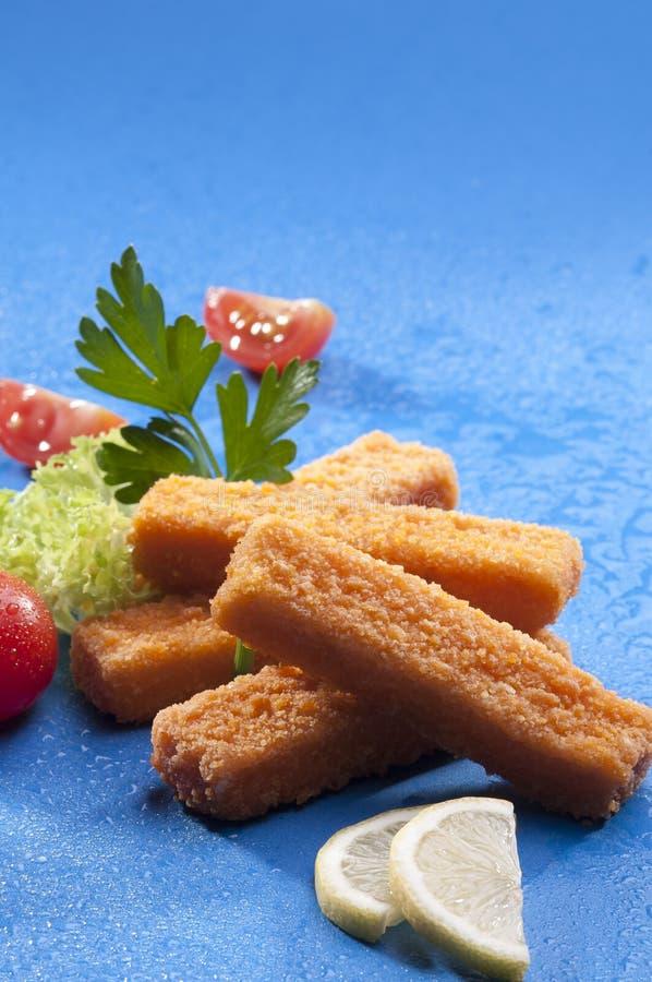 Τα πασπαλισμένα με ψίχουλα τηγανισμένα δάχτυλα ψαριών με την κόκκινη ντομάτα μαρουλιού και κερασιών με τη φέτα λεμονιών στο μπλε  στοκ εικόνα