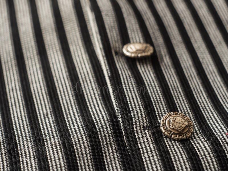Τα παλαιά κουμπιά σε ένα υπόβαθρο φανέλλων μαύρων ` s με τα σκοτεινά λωρίδες, κλείνουν επάνω στοκ φωτογραφία με δικαίωμα ελεύθερης χρήσης