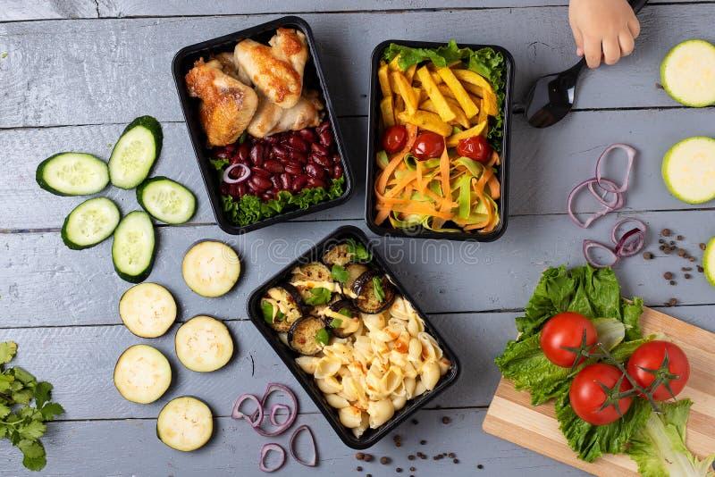 Τα πεδία εμπορευματοκιβωτίων τροφίμων και το χέρι κοριτσιών κρατούν το κουτάλι, τα ακατέργαστα λαχανικά, το zuchini και τις μελιτ στοκ εικόνα με δικαίωμα ελεύθερης χρήσης