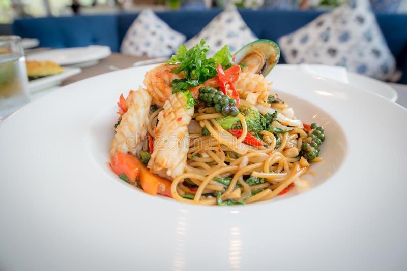 Τα πικάντικα μακαρόνια θαλασσινών ανακατώνουν το τηγανισμένο μαξιλάρι Cha που κυλιέται στο δίκρανο στο άσπρο πιάτο του εστιατορίο στοκ φωτογραφίες