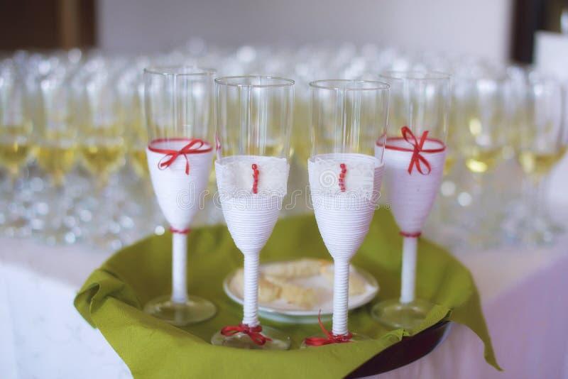 Τα πλήρη γυαλιά αφρώδους ή της σαμπάνιας με τέσσερις διακοσμημένους αυτούς χώρισαν σε έναν πράσινο δίσκο, για τη νύφη, το νεόνυμφ στοκ φωτογραφία με δικαίωμα ελεύθερης χρήσης