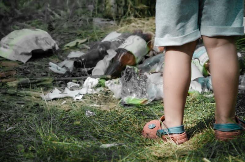 Τα πλαστικά απόβλητα είναι διασκορπισμένα στο δάσος, μπροστά τους ένα παιδί στοκ φωτογραφίες με δικαίωμα ελεύθερης χρήσης