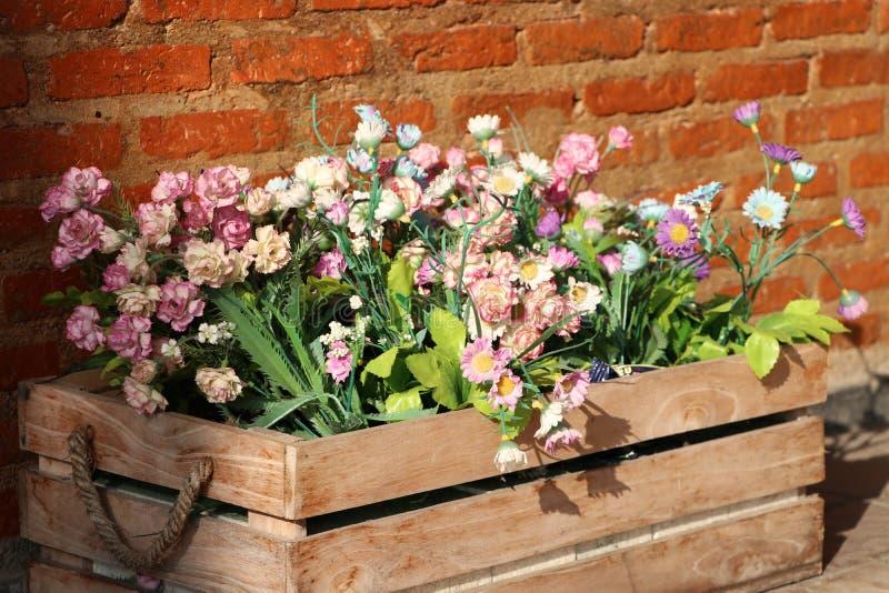 Τα πλαστικά λουλούδια και τα πράσινα φύλλα διακοσμούν στο ξύλινο κλου στοκ φωτογραφία