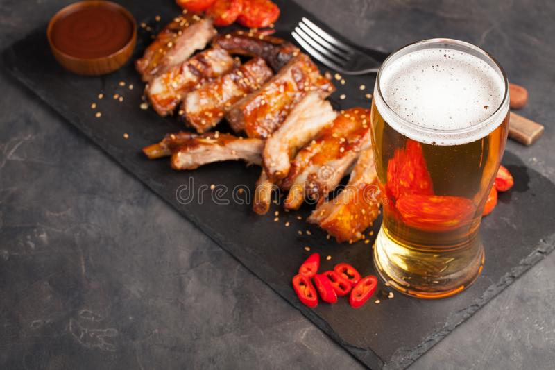 Τα πλευρά χοιρινού κρέατος στη σάλτσα και το μέλι σχαρών έψησαν τις ντομάτες και ένα ποτήρι της μπύρας σε ένα μαύρο πιάτο πλακών  στοκ εικόνες