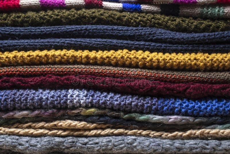 Τα πολύχρωμα, θερμά, πλεκτά, φωτεινά μάλλινα μαντίλι συσσωρεύονται το ένα στο άλλο σε έναν σωρό, έτοιμο για την αρχή ενός κρύου χ στοκ εικόνες