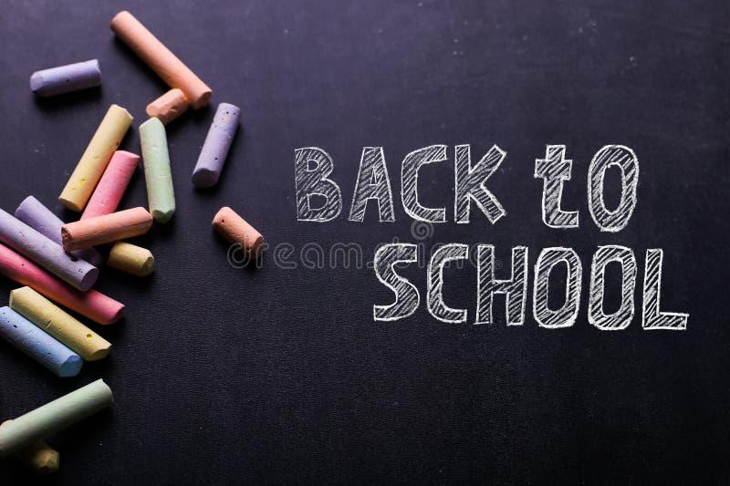 Τα πολύχρωμα κραγιόνια βρίσκονται σε έναν μαύρο πίνακα κιμωλίας, διάστημα αντιγράφων Η έννοια του σχολείου, της εκπαίδευσης και τ στοκ εικόνα με δικαίωμα ελεύθερης χρήσης