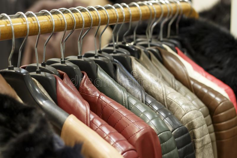 Τα πολύχρωμα σακάκια δέρματος κρεμούν στις κρεμάστρες στο κατάστημα στοκ εικόνες