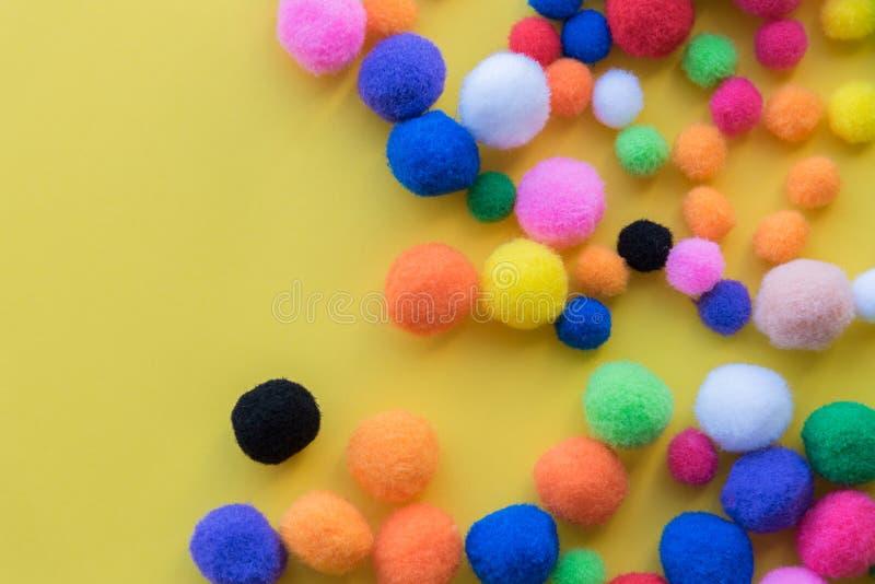 Τα πολύχρωμα pom-poms στα ανάμεικτα μεγέθη στο στερεό κίτρινο επίπεδο υποβάθρου βάζουν τη ρύθμιση στοκ φωτογραφία
