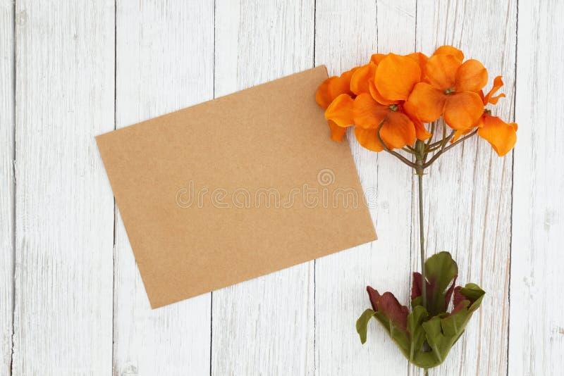 Τα πορτοκαλιά και κόκκινα λουλούδια πτώσης με την κενή ευχετήρια κάρτ στοκ φωτογραφίες