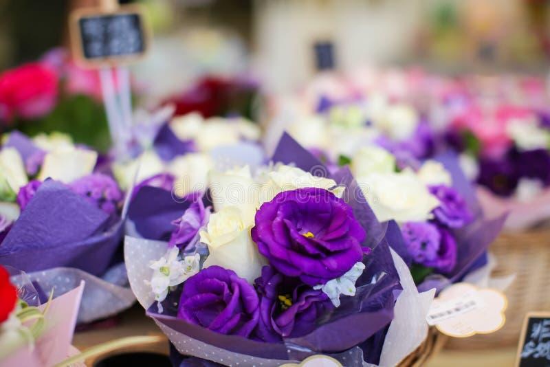 Τα πορφυρά τριαντάφυλλα Beautyful για την πώληση στο κατάστημα ανθοκόμων ` s στην οδό ανθίζουν την αγορά με το διαφανές τυλίγοντα στοκ φωτογραφία με δικαίωμα ελεύθερης χρήσης