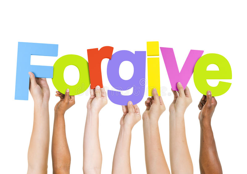 Τα πολυ-εθνικά χέρια που κρατούν το Word συγχωρούν στοκ εικόνες με δικαίωμα ελεύθερης χρήσης